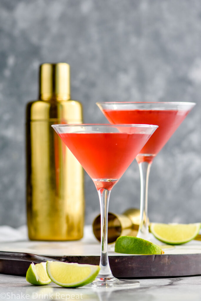 two martini glasses of Woo Woo surrounded by slices of lime and cocktail shaker