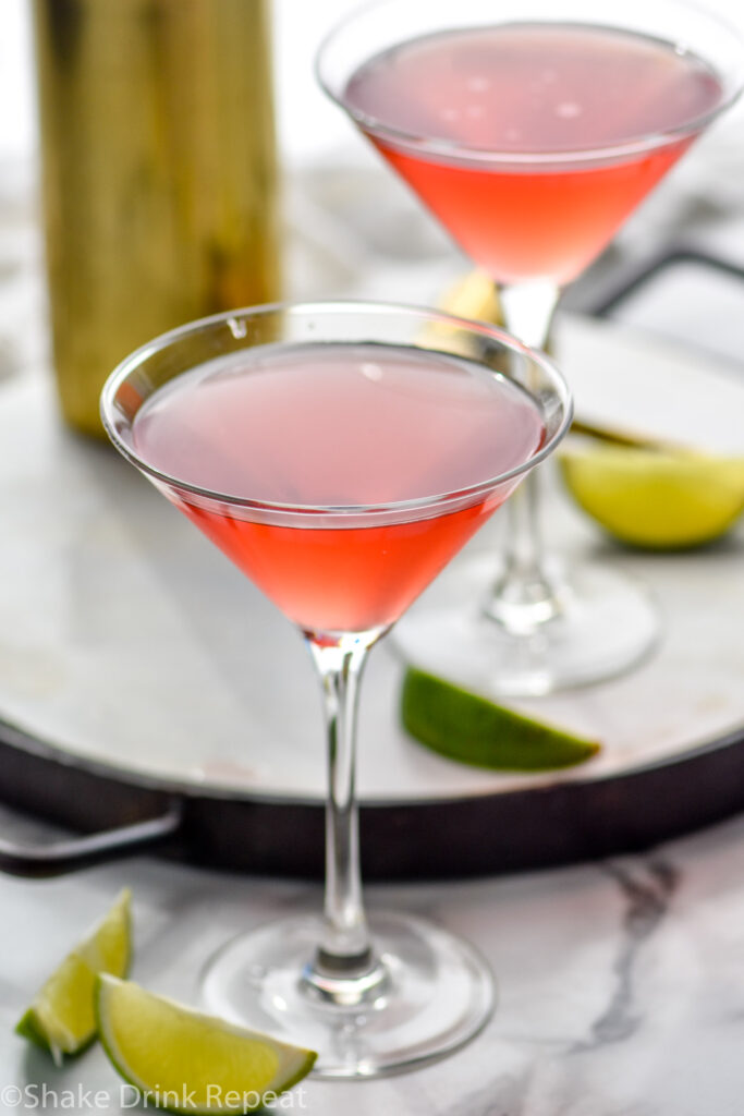 two martini glasses of Woo Woo surrounded by slices of lime
