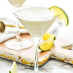 two martini glasses of Key Lime Martini recipe surrounded by slices of lime