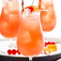three glasses of Sex on The Beach with ice, straws, orange slices, and maraschino cherries for garnish