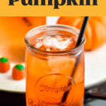 glass of Drunk Pumpkin cocktail recipe with ice, straw and surrounded by pumpkin candies