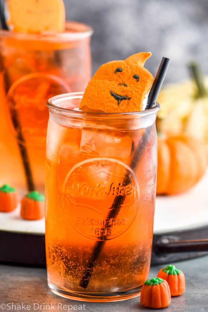 two glasses of Drunk Pumpkin cocktail recipe with ice, straw, and garnished with pumpkin peep candy