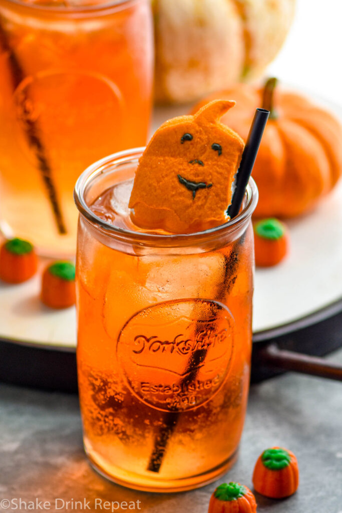 two glasses of drunk pumpkin cocktail recipe with ice, straws, and garnished with pumpkin candies