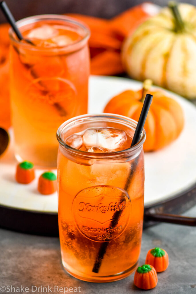 two glasses of Drunk Pumpkin cocktail with ice and straws and surrounded by pumpkin candy