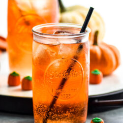 two glasses of Drunk Pumpkin cocktail recipe with ice, straw, and surrounded by pumpkin candy